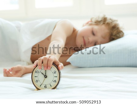 Little boy's hand reaching for the alarm clock to turn it off.