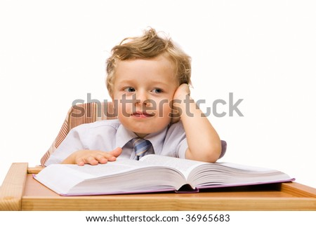 Little boy sitting at the desk and reading book