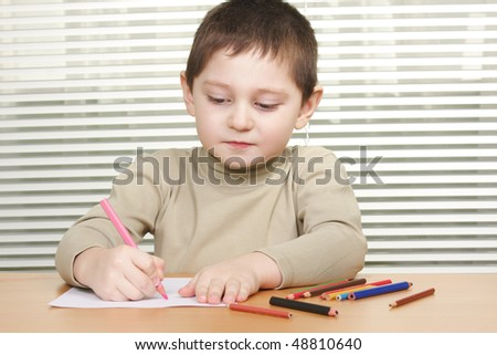 Little boy sitting at wooden desk drawing with pink pencil