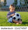 Little boy sitting barfoot on the green grass in the goal with his soccer ball on his lap lost in thought - stock photo