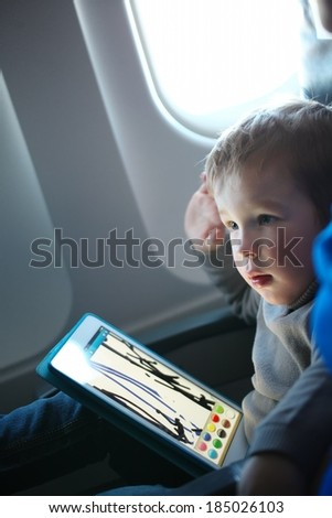 Little boy sitting in his seat during a flight and painting on a tablet computer in an airplane