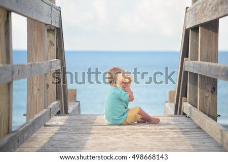 Little boy sitting on boardwalk with stairs to the beach, holding huge seashell, playing with it.