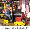 Little boy sitting on locomotive on carousel - stock photo