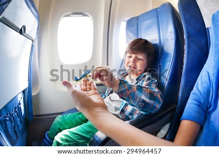 Little boy takes little plane from moms hand sitting by the window in jet airplane