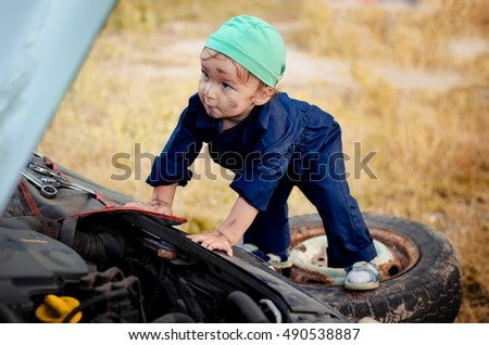 Little boy (Toddler) mechanic repairing the car in the yard of his house