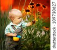 little boy with a watering can check the quality of flowers - stock photo