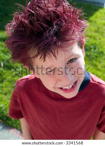 Little boy with crazy hair winks at the camera