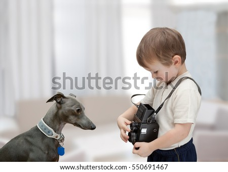 Little boy with old camera photographs his dog