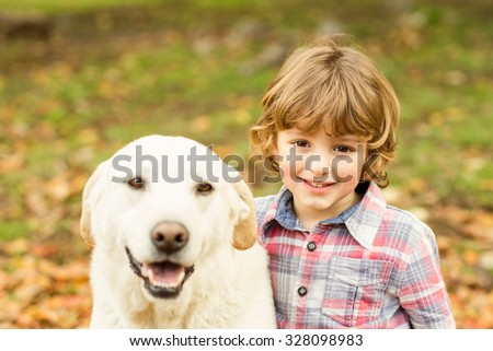 Little boys with his dog on an autumns day