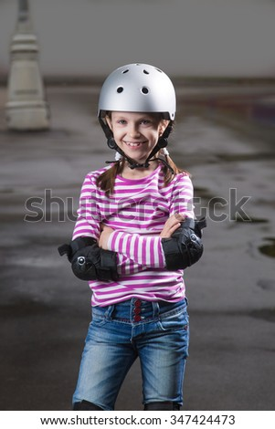 Little caucasian cute girl wearing a roller protection and helmet