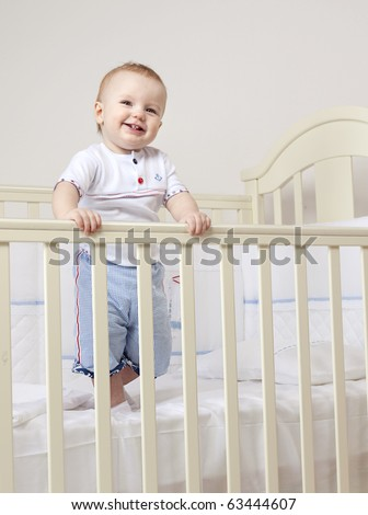 little child baby smiling standing in bed