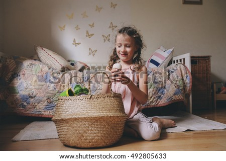 little child girl playing in her room with toy food, cooking and having fun at home