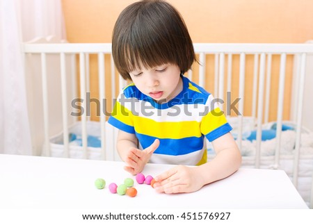 Little child (2 years) modelling playdough balls at home