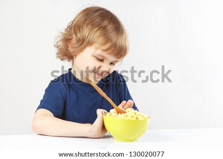 Little cute blonde boy refuses to eat a cereal