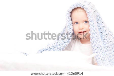 Little cute boy under blanket sitting on the bed (after taking bath)
