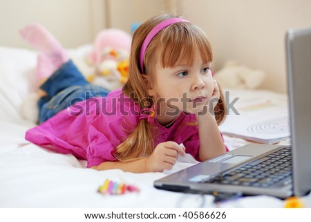 Little cute child playing with laptop at home