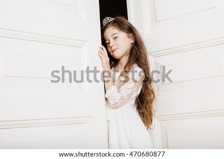 little cute girl at home opening door well-dressed in white dress adorable