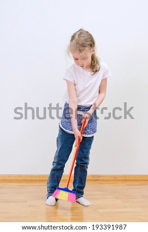 Little cute girl brooming floor at home.
