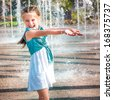 little cute girl having fun in splashes a fountain - stock photo