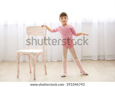 Little cute girl in pink leotard making new ballet movement near chair at dance studio