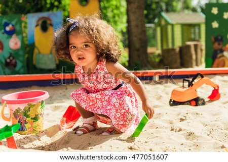 little cute girl playing in the sandbox