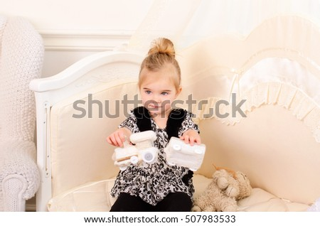 Little cute girl plays toy knitted train sitting in  bright room
