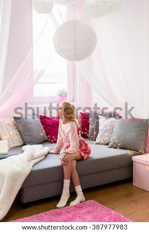 Little cute girl sitting on sofa in her stylish room