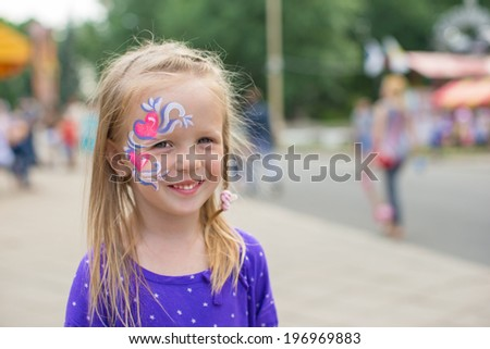 Little cute girl with a pattern on the face outdoor