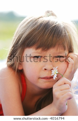 Little cute girl with flower outdoors