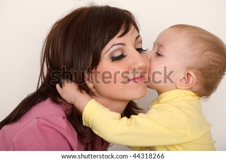 Little daughter kissing her mother. Close up. Horizontal format.