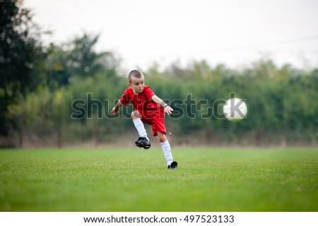 Little football player in red uniform shooting the ball