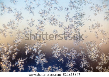 Little frosty patterns on glass, visible snowflakes. Winter in Russia.