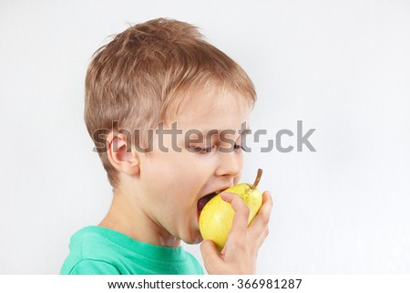 Little funny boy in a green shirt eating a yellow pear