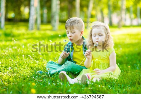 Little girl and boy blowing dandelion together