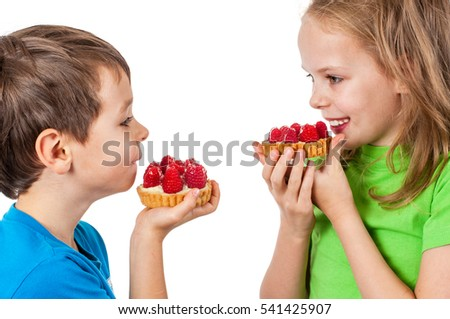 Little girl and boy eating cakes with fruits.
