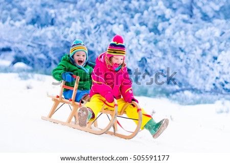 Little girl and boy enjoy a sleigh ride. Child sledding. Toddler kid riding a sledge. Children play outdoors in snow. Kids sled in Alps mountains in winter. Outdoor fun for family Christmas vacation.
