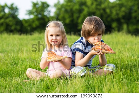 Little girl and boy outdoor summer with pizza