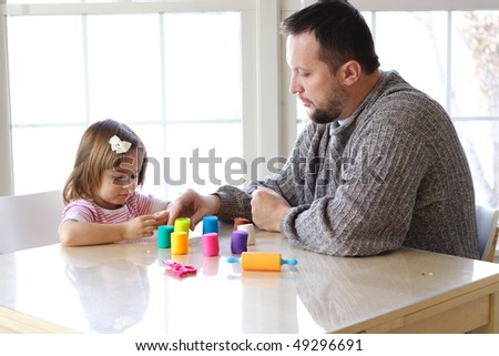 Little girl and father creating toys from play dough