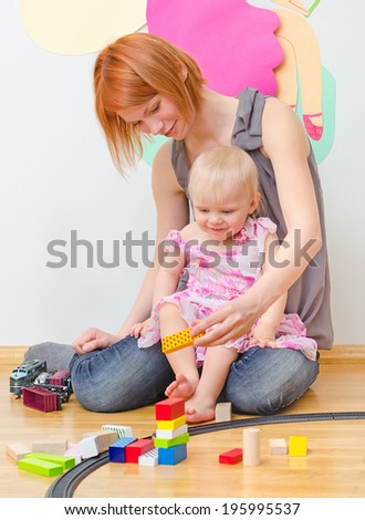 Little girl and her mother playing with railway sitting on the floor.
