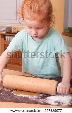Little girl baking rolling pastry for Christmas cookies