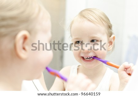 Little girl brushing her teeth in bathroom