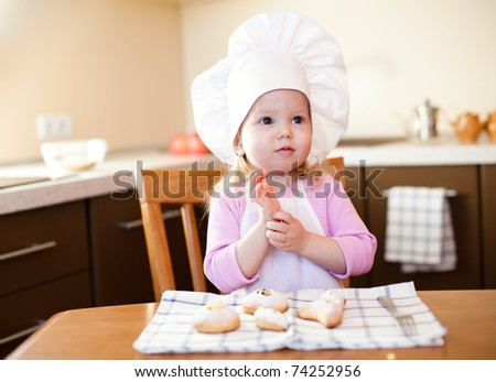 Little girl clears hands on kitchen