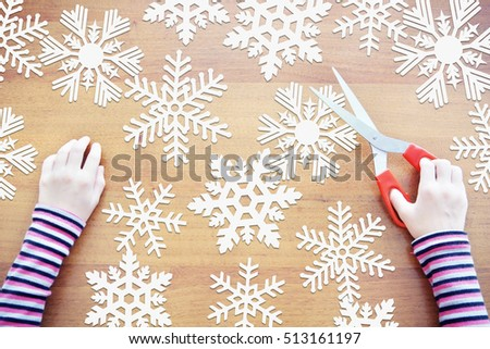 Little girl cuts many paper snowflakes. Preparation to New Year holiday. Concept with paper scrapbooking