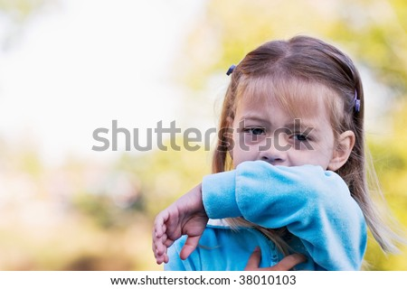Little girl demonstrates coughing or sneezing into her elbow to avoid spreading unwanted germs.