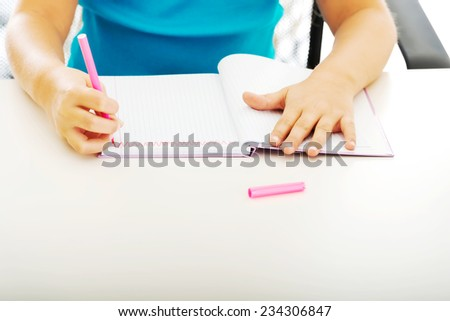 Little girl drawing in note using marker
