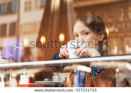 Little girl drinking hot chocolate in a cafe