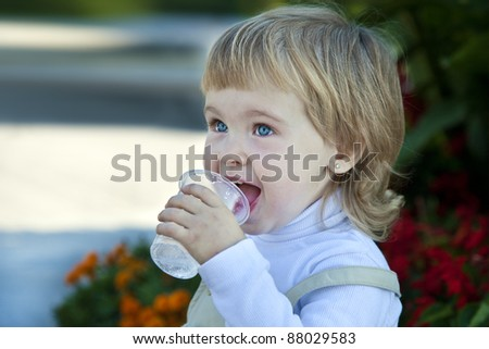 little girl drinks water in summer day