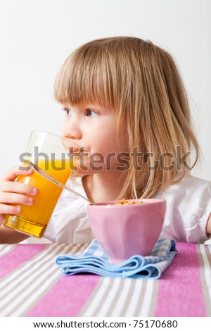 Little girl eating cereal and drinking orange juice.