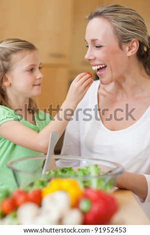 Little girl feeding her mother with salad