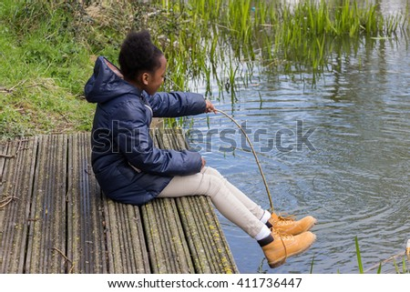 Little girl fishing with a stick in a pond